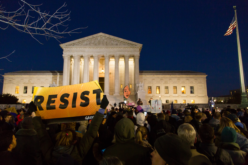 "A photo showing a crowd of people protesting at night outside of the US Supreme court. In the foreground, there is a person holding a sign that reads ""RESIST."""